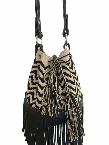 Side angle image of Wayuu mochila purse with black leather strap and fringe; bag is tan with black zigzags