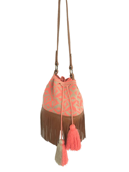 Image of Wayuu bucket bag purse with brown leather strap and fringe; bag is tan with coral pink design