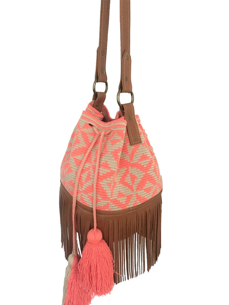 Side angle image of Wayuu bucket bag purse with brown leather strap and fringe; bag is tan with coral pink design