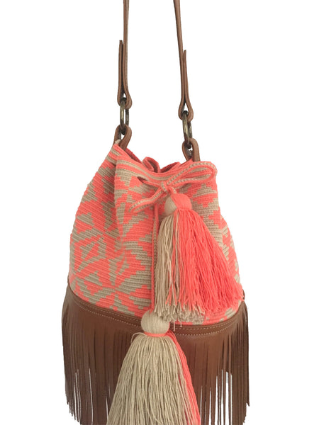 Close up image of Wayuu bucket bag purse with brown leather strap and fringe; bag is tan with coral pink design