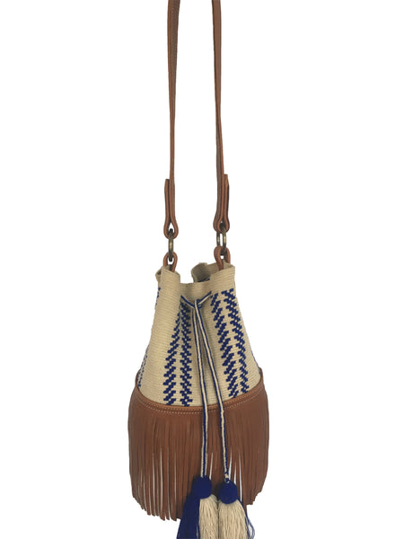 Image of Wayuu bucket bag purse with brown leather strap and fringe and tassels; bag is light tan with blue design