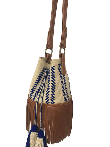 Side angle image of Wayuu bucket bag purse with brown leather strap and fringe and tassels; bag is light tan with blue design