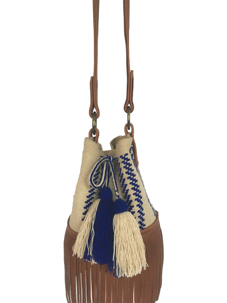 Close up image of Wayuu bucket bag purse with brown leather strap and fringe and tassels; bag is light tan with blue design