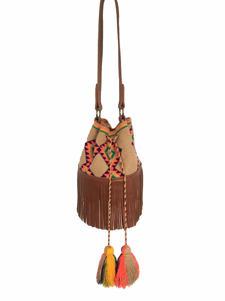 Image of Wayuu bucket bag purse with brown leather strap and fringe; bag is tan with purple, bright yellow, green and orange design