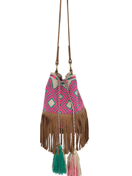 Image of Wayuu bucket bag purse with brown leather strap and fringe; bag is tan with bright pink and turquoise design