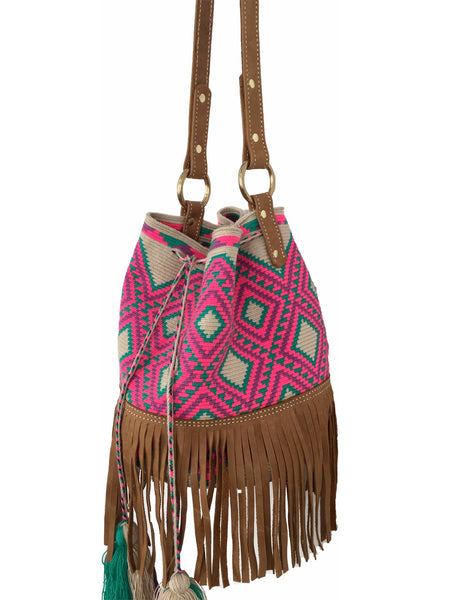 Side angle image of Wayuu bucket bag purse with brown leather strap and fringe; bag is tan with bright pink and turquoise design