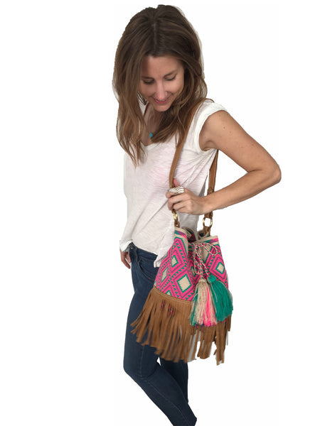 On body image of Wayuu bucket bag purse with brown leather strap and fringe; bag is tan with bright pink and turquoise design
