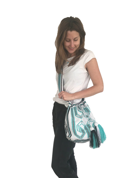On body image of Wayuu mochila purse, drawstring crossbody bag with tassels and cloth strap; white base with black and teal design