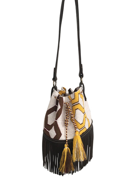 Image of Wayuu bucket bag purse with brown leather strap and fringe; bag is white base with yellow and brown design