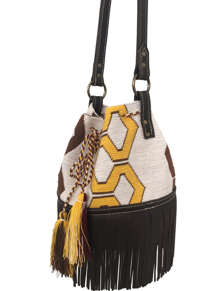 Side angle image of Wayuu bucket bag purse with brown leather strap and fringe; bag is white base with yellow and brown design