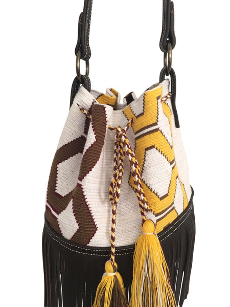 Close up image of Wayuu bucket bag purse with brown leather strap and fringe; bag is white base with yellow and brown design