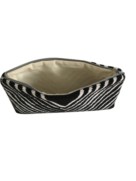 Interior image of lining of Wayuu small clutch purse; rectangular shape black and white striped in a V shape