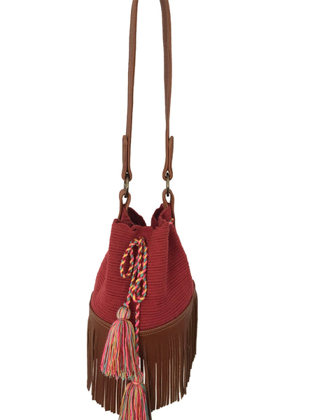 Image of Wayuu bucket bag purse with brown leather strap and fringe; bag is solid raspberry red with colorful tassels