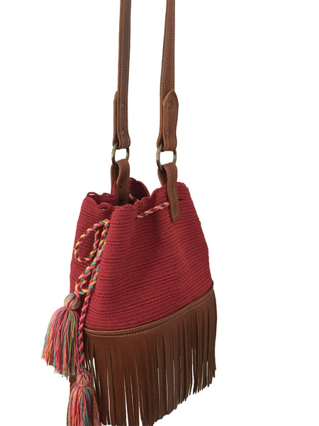 Side angle image of Wayuu bucket bag purse with brown leather strap and fringe; bag is solid raspberry red with colorful tassels