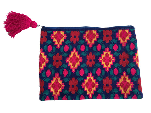 Image of Wayuu clutch purse with pink tassel and zipper; rectangular shape with royal blue base and bright multi color design