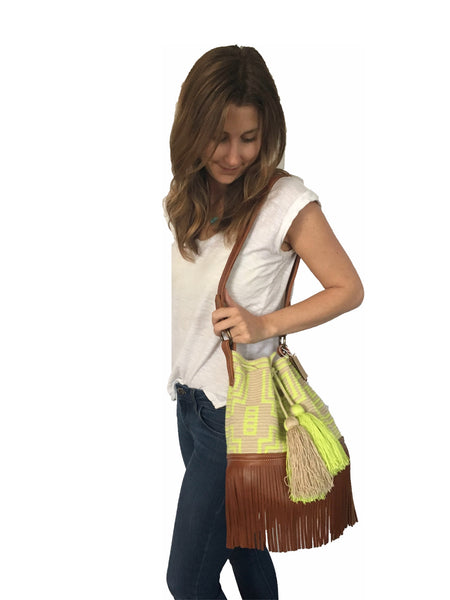 On body image of Wayuu bucket bag purse with brown leather strap and fringe; bag is light tan with neon yellow design