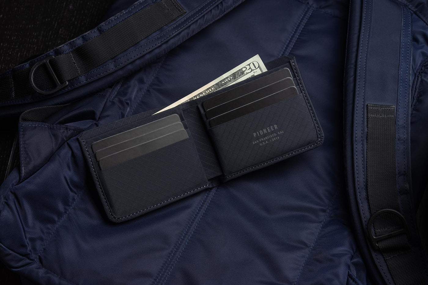 Pioneer division billfold wallet with cash navy sitting on backpack