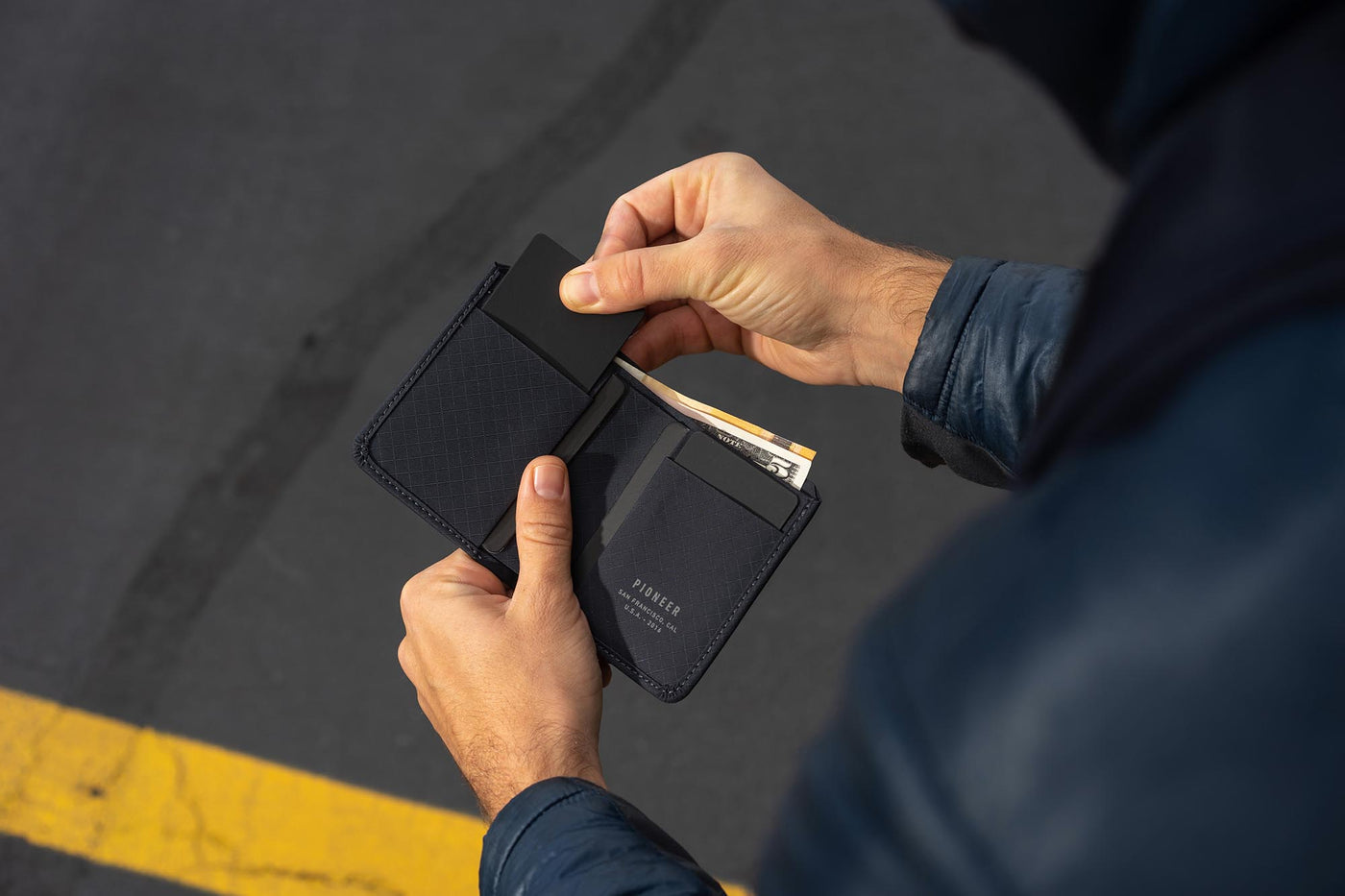 altitude billfold wallet navy with dollars and euros being used by a man