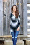 Front view of women's long sleeve black and grey striped v-neck shirt with jeans