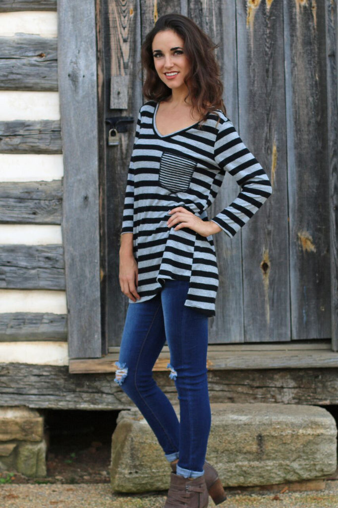 Side view of women's long sleeve black and grey striped v-neck shirt with dark wash jeans and brown booties