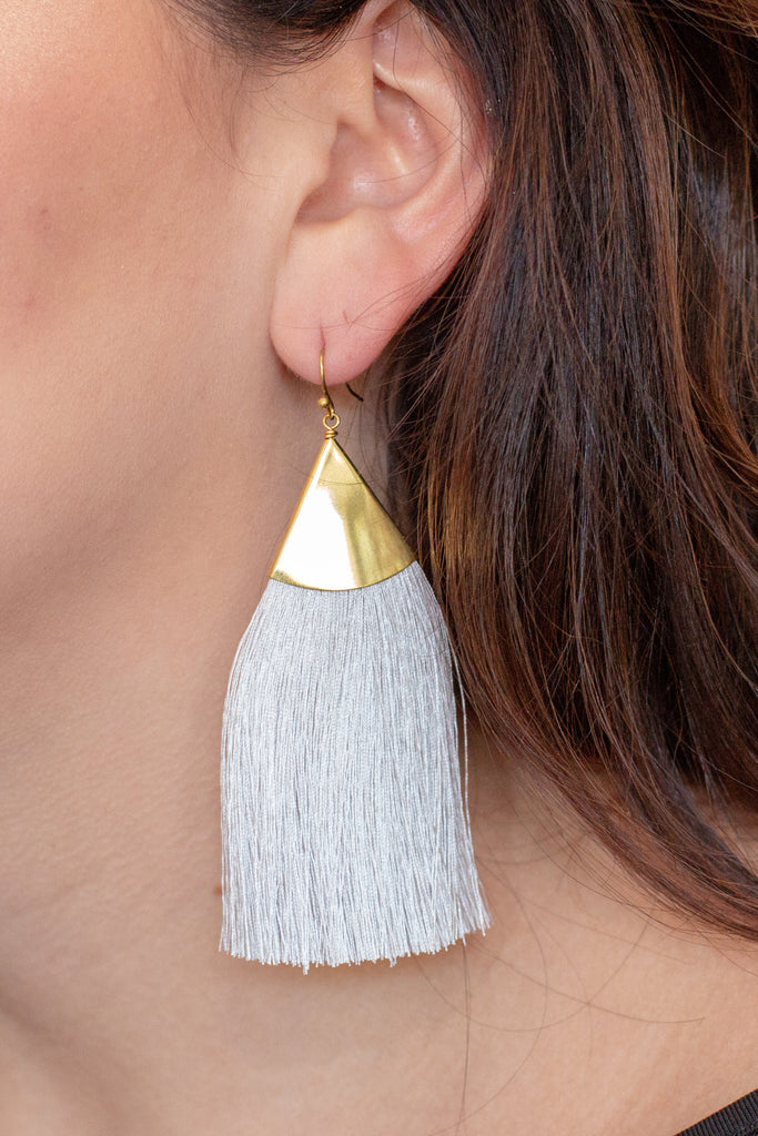 Left angle of model with Caroline Hill grey and gold drop tassel earrings.