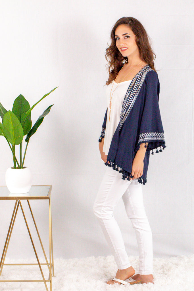 Navy Kimono Style Cardigan with White Embroidered Neck/Sleeves and Pom Trim Side Left View