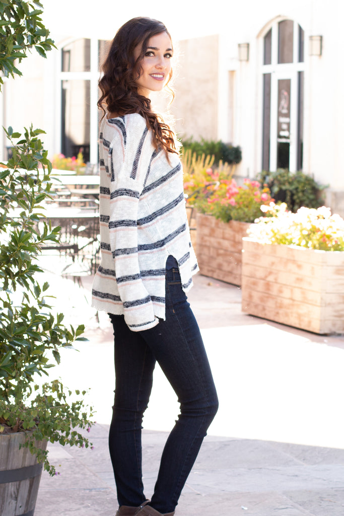 White and Gray/Pink Striped Slouchy Sweater with Slit Hem w/ Jeans Right Side View