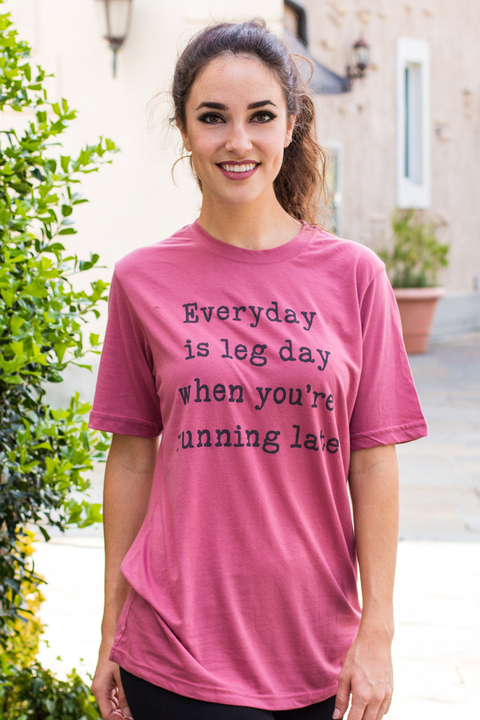 "Front closeup of model in women's Ady Belle ""Everyday is leg day when you're running late"" hot pink tee."