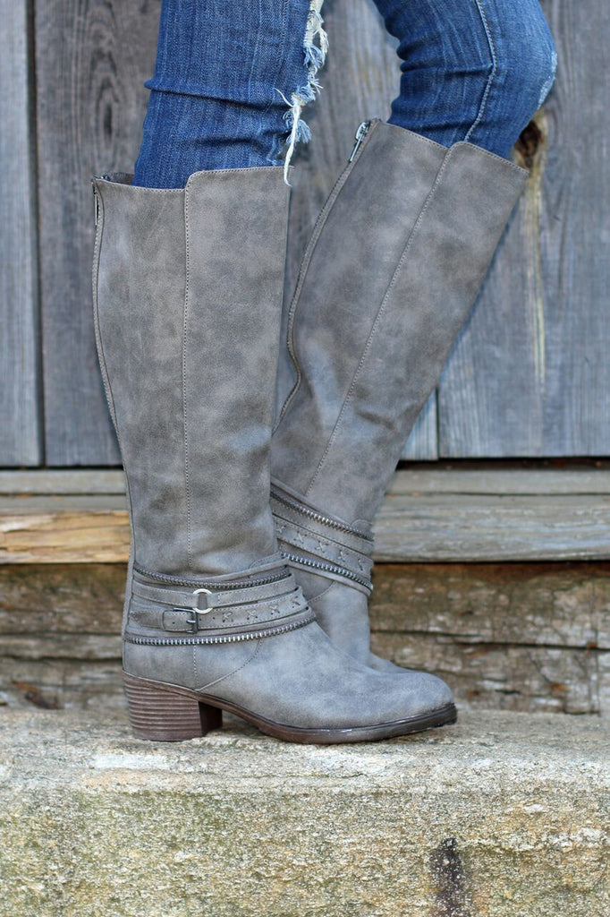 Side view of women's heeled grey leather riding boots with strap details