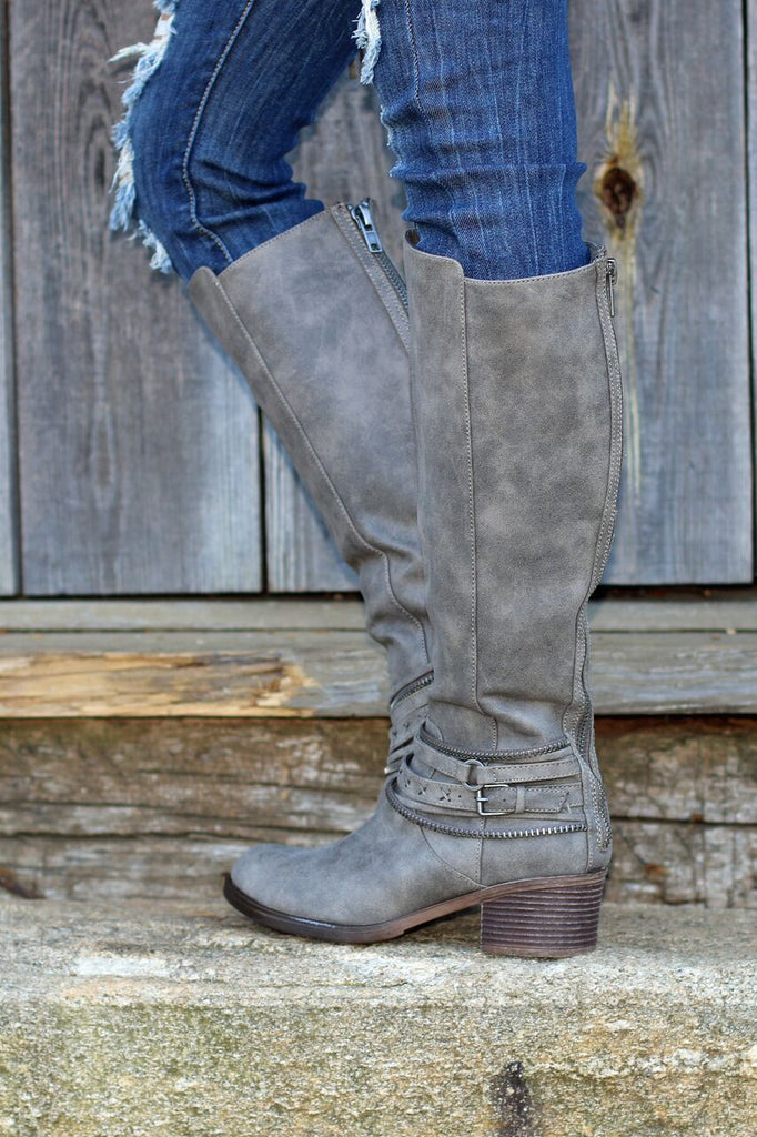 Side view of women's heeled grey leather riding boots with studded ankle straps