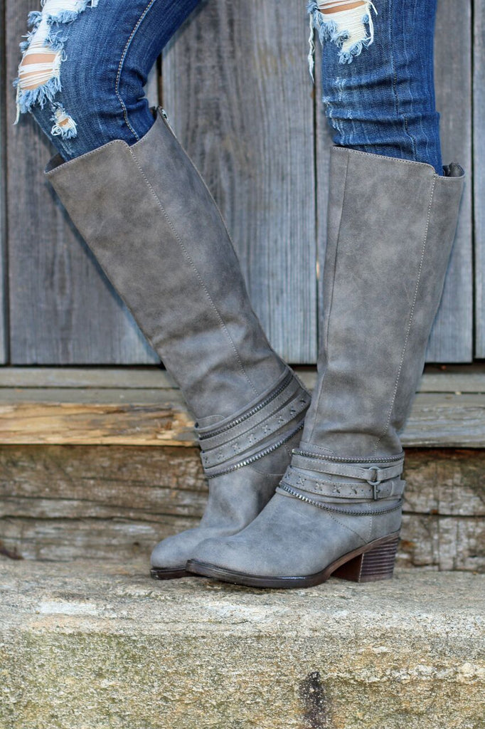 Front view of women's grey leather riding boots with rounded toe and studded buckles