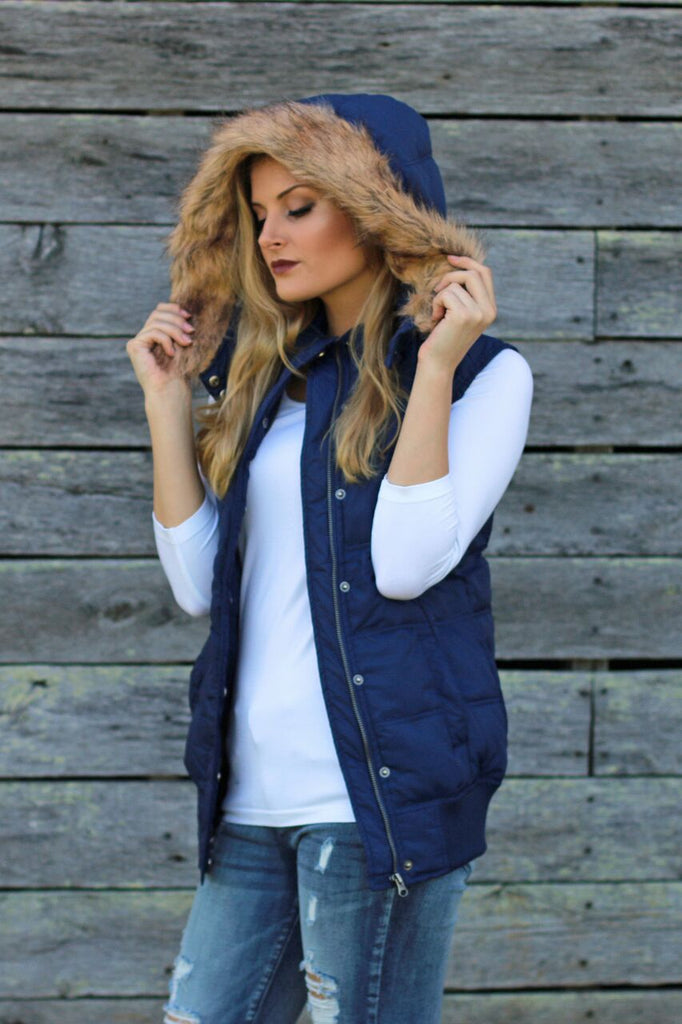 Side view of women's navy blue puffer vest with dirty blonde faux fur lined hood and snap buttons with form fitting white 3/4 sleeve shirt underneath and ripped jeans