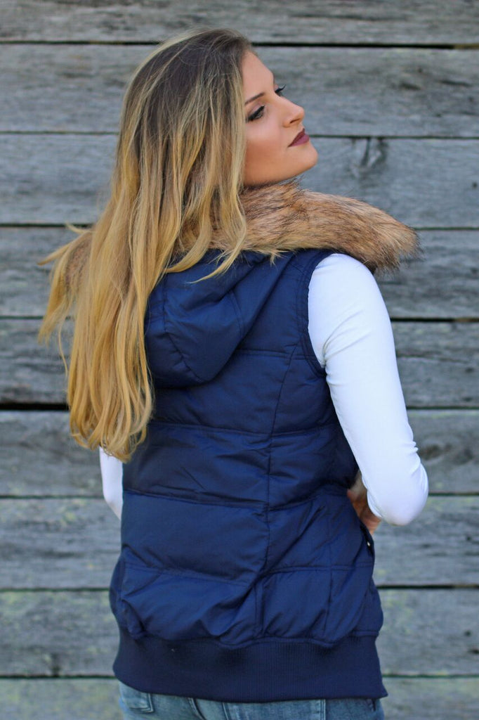 Back view of women's navy blue puffer vest with dirty blonde faux fur lined hood and fitted white 3/4 sleeve shirt underneath