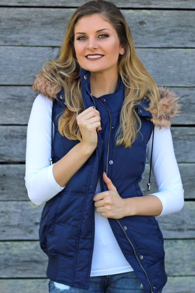 Front view of women's hooded, faux fur lined navy blue puffer vest with white 3/4 sleeve top