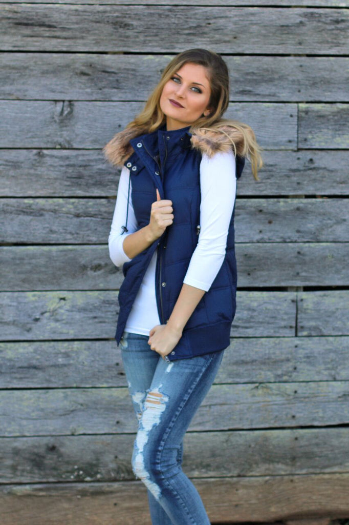 Side view of women's navy blue puffer vest and faux fur lined hood with tight white 3/4 sleeve shirt underneath and destroyed skinny jeans