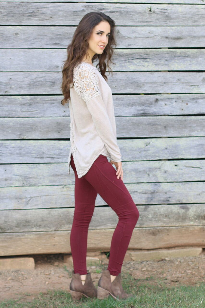 Side view of  juniors beige long sleeve shirt with lace shoulder accents, split back design, red moto leggings, and brown cutout booties