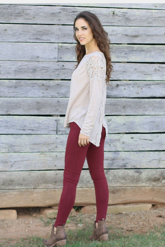 Side view of women's and juniors beige long sleeve shirt with lace shoulder accents, red moto leggings, and brown booties