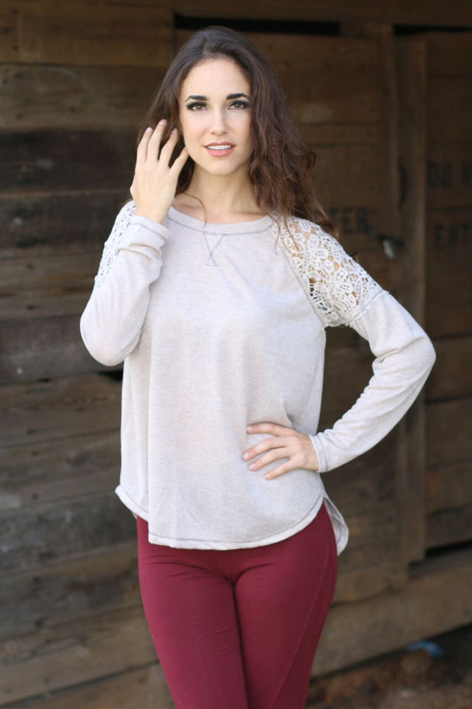 Close up front view of women's beige long sleeve shirt with lace shoulder accents and red legging pants