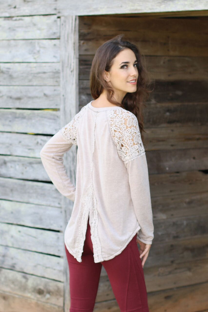 Back view of women's beige long sleeve shirt with lace split back and red legging pants