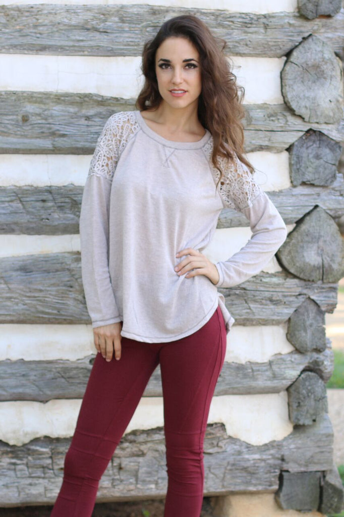 Front view of juniors beige long sleeve lace shirt with lace shoulders, split back, and thick red moto leggings