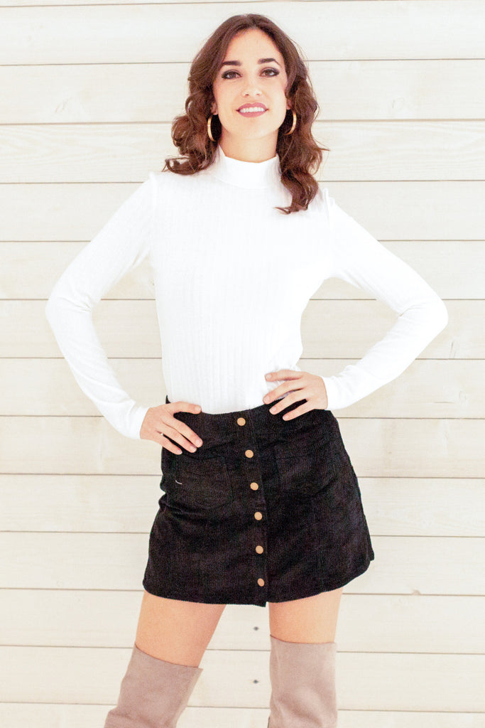 black button up mini skirt with pockets and fitted white mockneck sweater