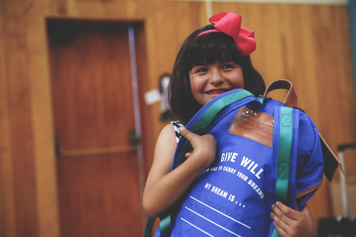 child holding give will backpack