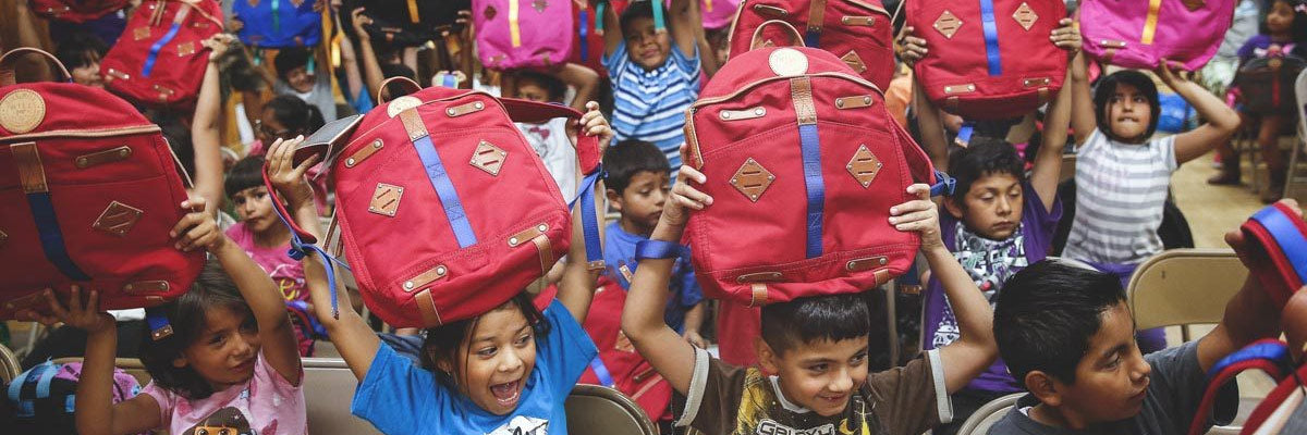 children happily showing off their new backpacks