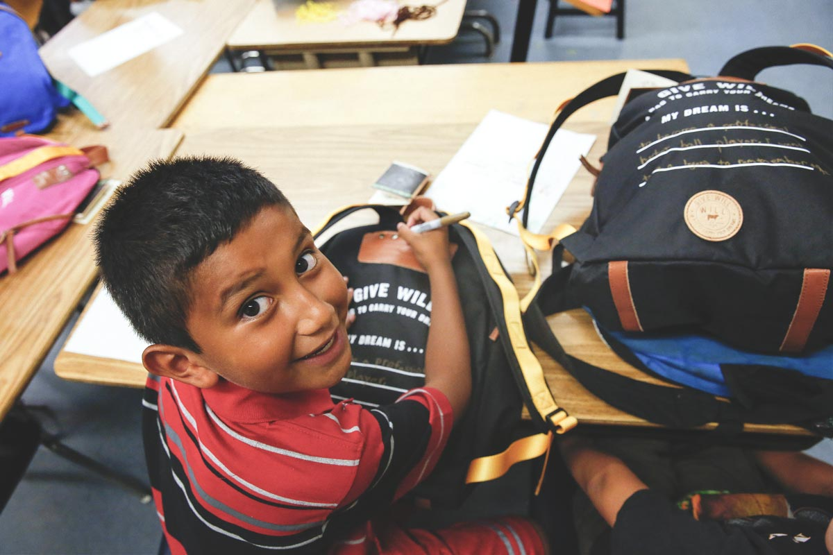 smiling boy holding a give will backpack