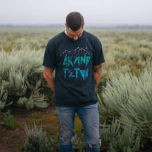 Load image into Gallery viewer, Male model wearing the Summit Outdoor Grand Teton National Park design on a black tshirt standing in a field