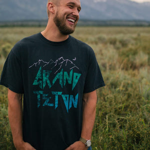 Male model smiling while wearing the Grand Teton National Park shirt