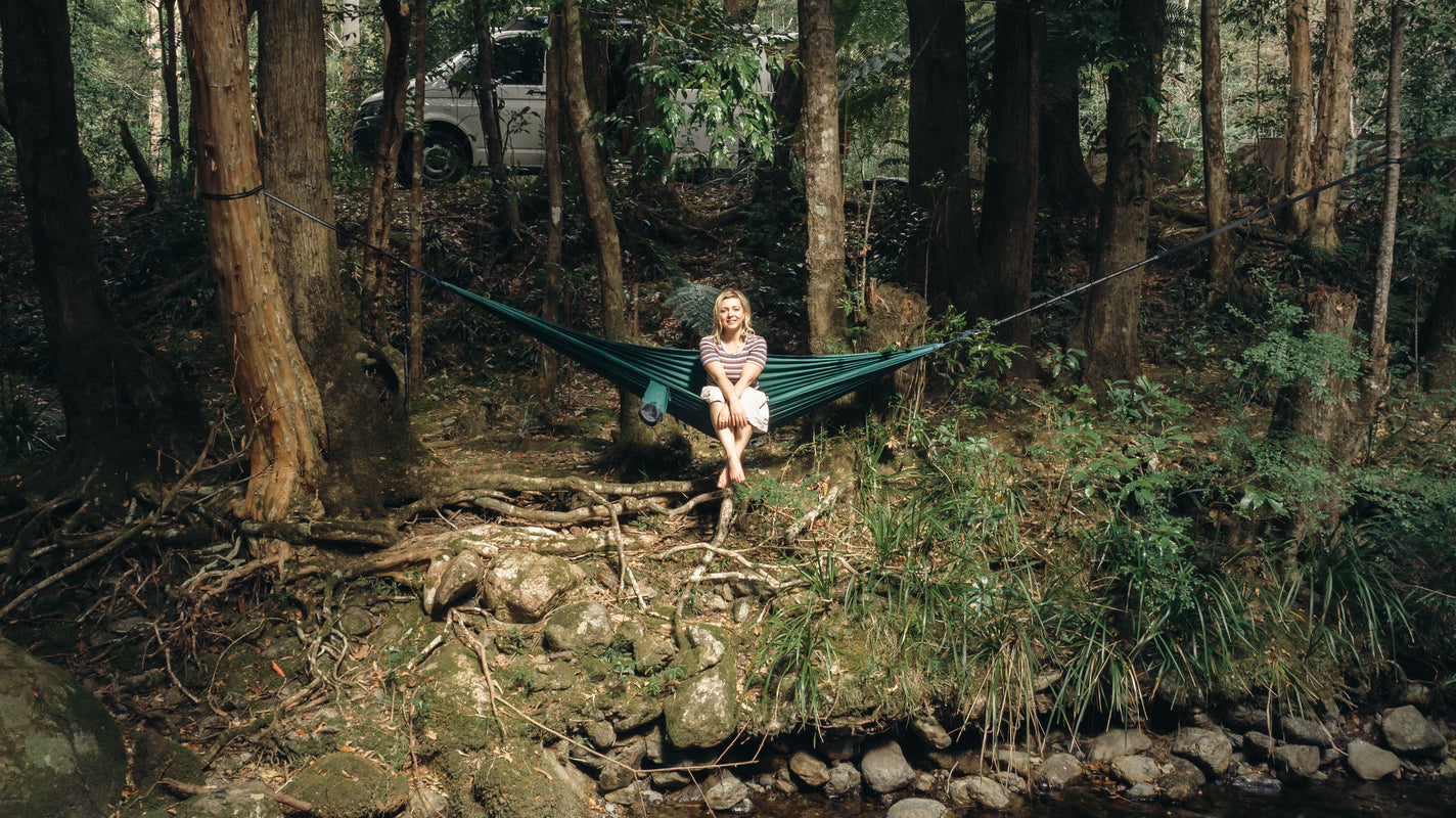 Lady sitting in hammock in forest