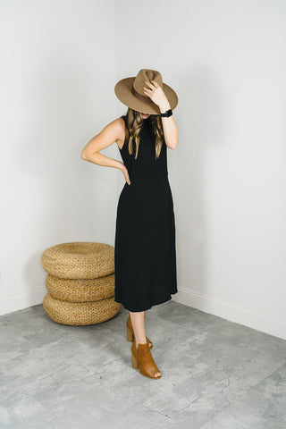 Woman wearing a black midi dress with tan booties and felt fedora