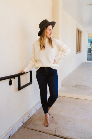 Woman wearing a classic ivory mock neck sweater in dark high rise denim jeans.