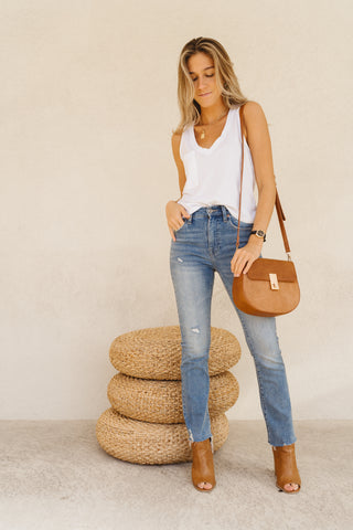 Woman wearing a white Zsupply Skimmer Tank with light skinny denim